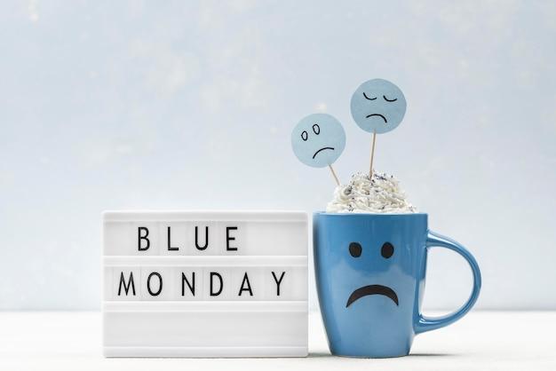 Vue de face de la tasse triste avec boîte à lumière pour lundi bleu
