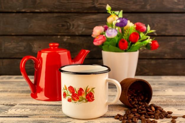 Vue de face de la tasse vide avec bouilloire rouge graines de café brun et fleurs sur le bureau en bois