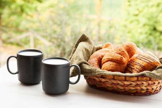 Vue de face des tasses à café avec des croissants