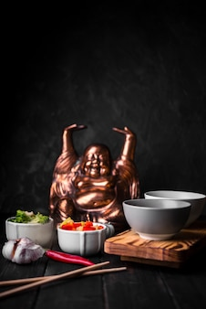 Vue de face de tasses de légumes avec statue