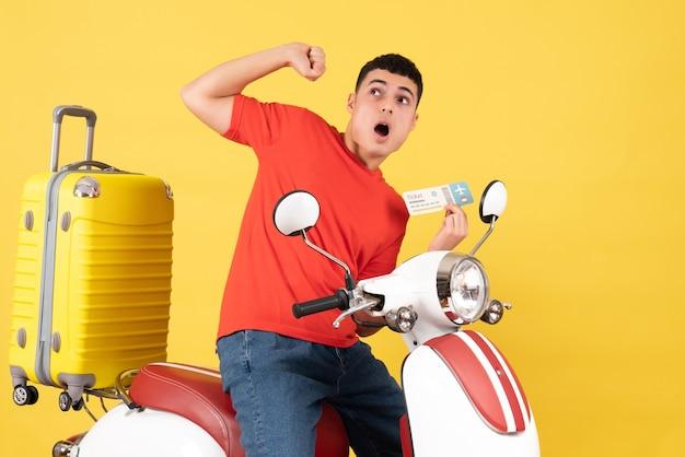 Vue de face terrifié jeune homme dans des vêtements décontractés sur un billet de tenue de cyclomoteur