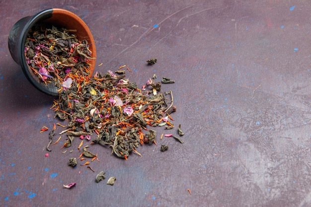 Vue de face thé frais séché sur fond sombre saveur de fleur de poussière de thé de plante