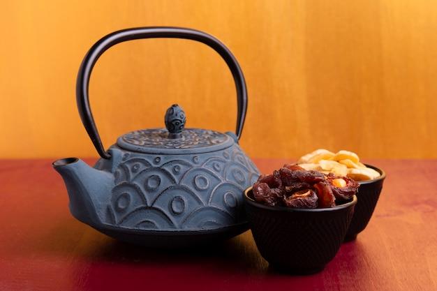 Vue de face de la théière et des mets délicats pour le nouvel an chinois