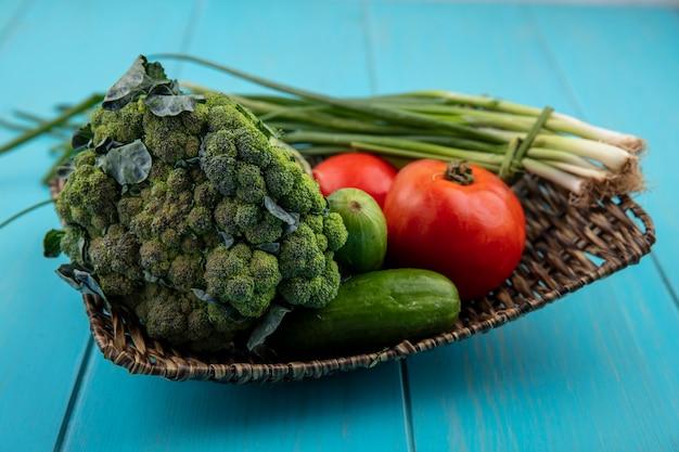 Vue de face tomates aux concombres oignons verts et brocoli sur un support sur un fond turquoise