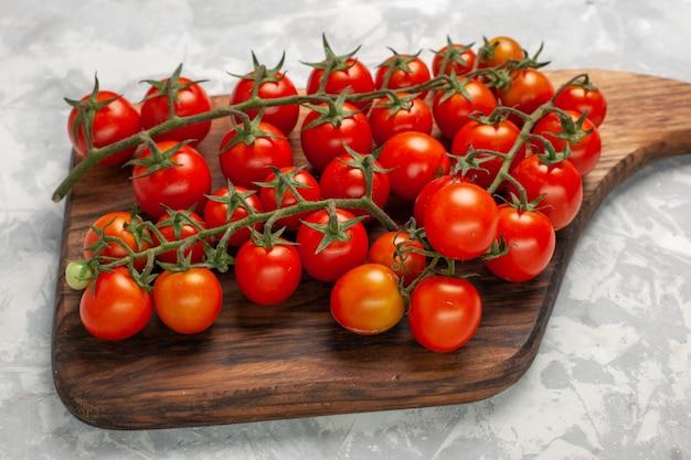 Vue de face tomates cerises fraîches légumes entiers mûrs sur surface blanche repas de légumes salade santé alimentaire