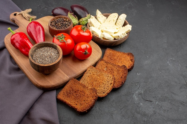 Vue de face des tomates fraîches avec des miches de pain noir et du fromage blanc sur un espace sombre