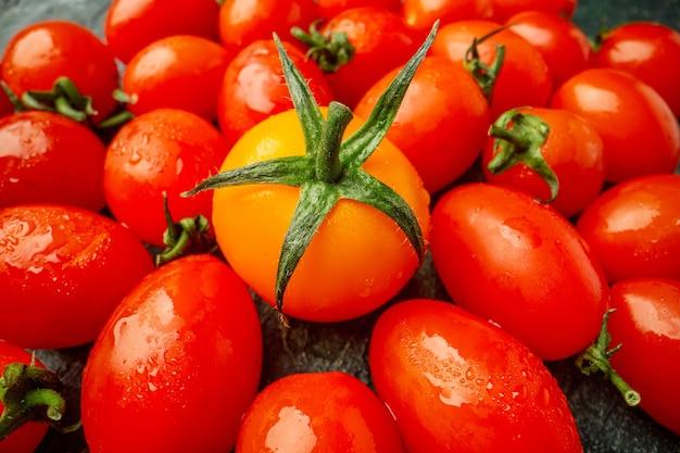 Vue de face des tomates oranges avec des tomates rouges sur une surface vert foncé
