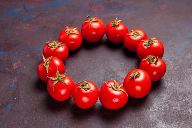 Vue de face des tomates rouges fraîches encerclées sur l'espace sombre