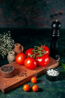 Vue de face tomates rouges fraîches sur fond sombre