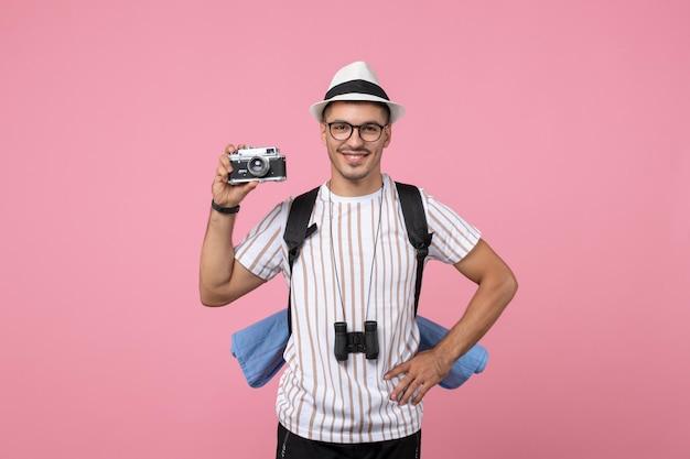 Vue de face touriste masculin prenant une photo avec appareil photo sur la couleur rose des émotions touristiques du mur