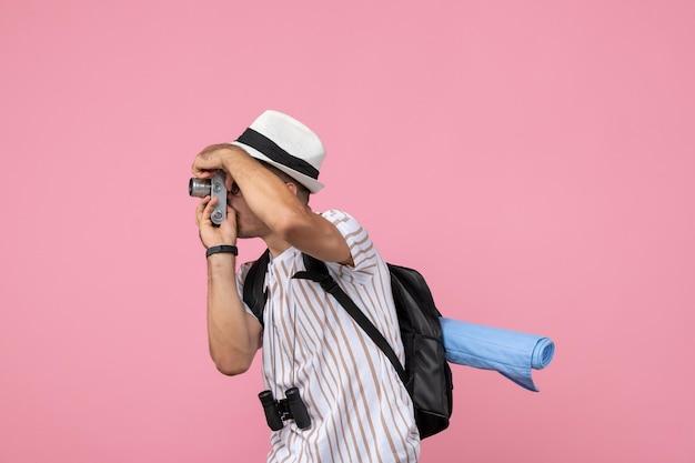 Vue de face touriste masculin prenant des photos avec l'appareil photo sur la couleur touristique de l'émotion au sol rose