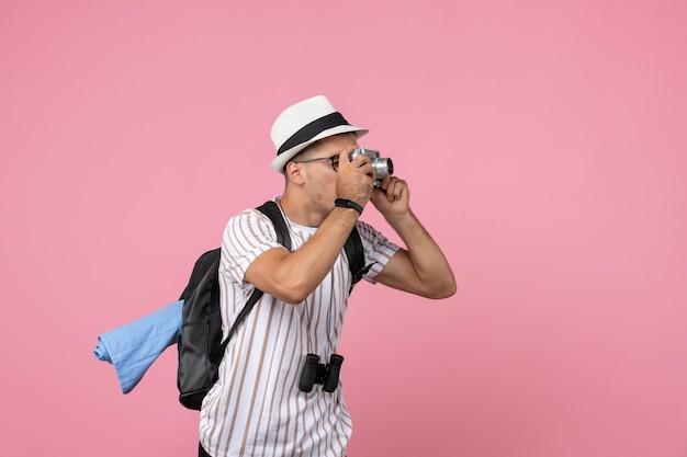 Vue de face touriste masculin prenant des photos avec appareil photo sur le mur rose émotion couleur touristique