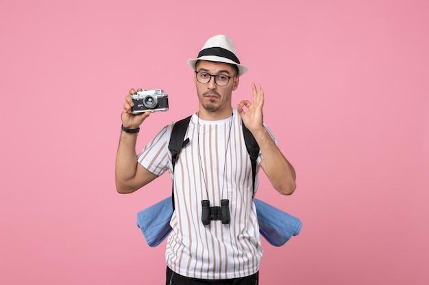 Vue de face touriste masculin tenant la caméra sur la couleur de l'émotion touristique du mur rose