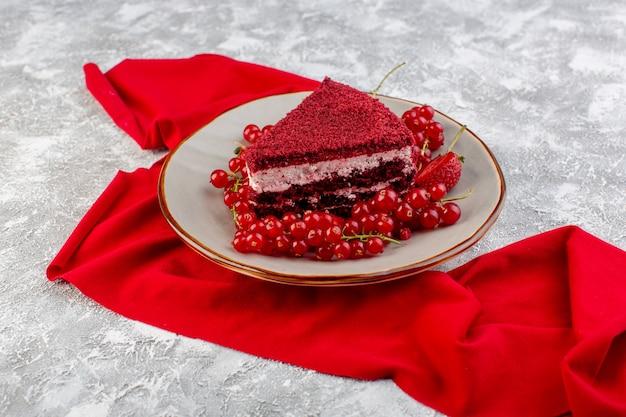 Vue de face tranche de gâteau rouge morceau de gâteau aux fruits à l'intérieur de la plaque avec des canneberges fraîches et des fraises sur le thé gris