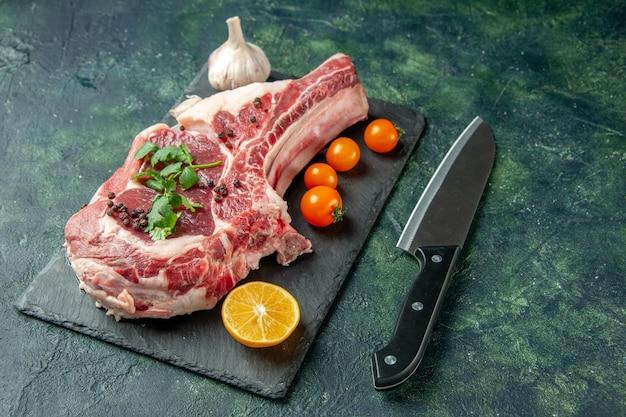 Vue de face tranche de viande fraîche avec tomates oranges sur bleu foncé nourriture viande cuisine animal poulet couleur vache boucher