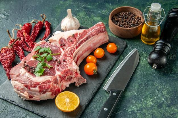Vue de face tranche de viande fraîche avec tomates oranges sur couleur bleu foncé nourriture viande cuisine animal poulet vache boucher