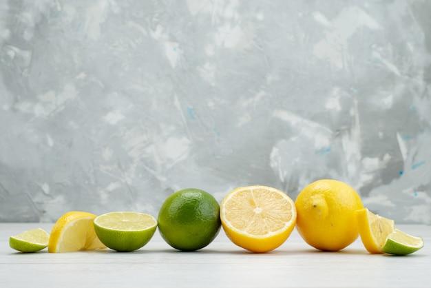 Vue de face en tranches de citron vert frais juteux et fruits aigres avec des citrons sur blanc