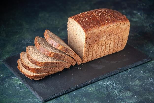 Vue de face de tranches de pain noir sur tableau noir sur fond de couleurs mélangées en détresse
