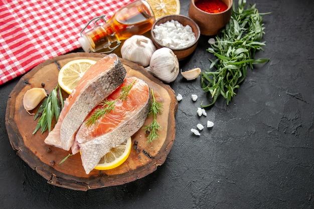 Vue de face tranches de poisson frais avec des tranches de citron ail et assaisonnements sur un plat de fruits de mer foncé couleur nourriture viande photo crue
