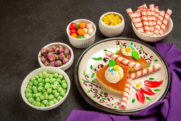 Vue de face des tranches de tarte crémeuses avec du tissu violet et des bonbons sur un espace gris