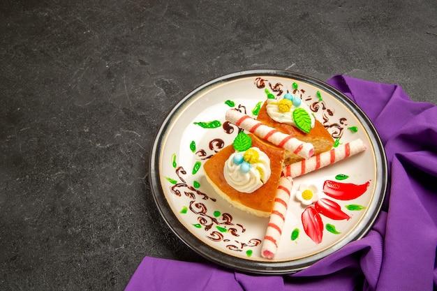 Vue de face des tranches de tarte crémeuses avec du tissu violet sur un espace gris