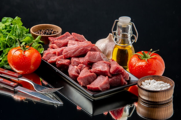 Vue de face des tranches de viande fraîche à l'intérieur d'un plateau noir avec des tomates et des légumes verts sur une table noire