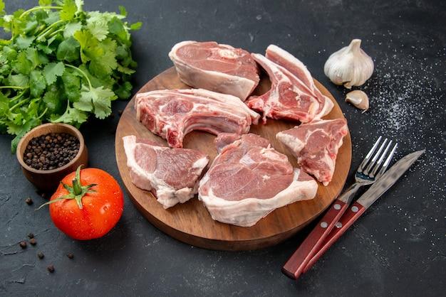 Vue de face tranches de viande fraîche viande crue avec des verts et des tomates sur fond sombre repas de cuisine nourriture vache plat de nourriture salade barbecue animal