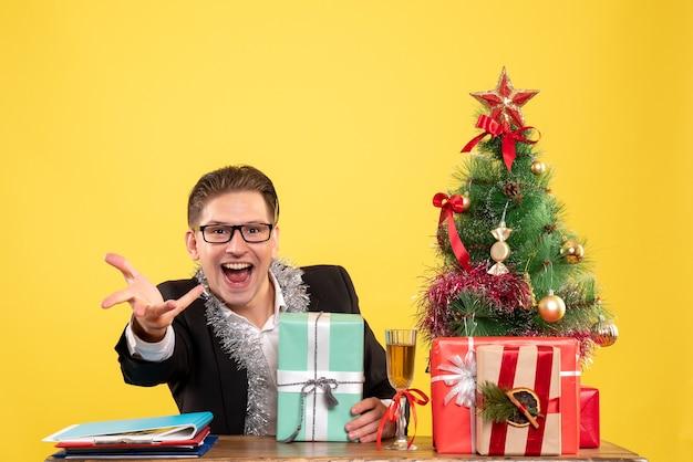 Vue de face travailleur masculin assis avec des cadeaux de noël et arbre