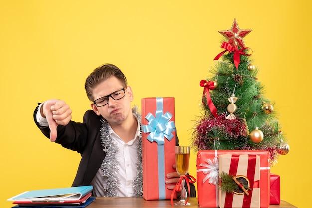 Vue de face travailleur masculin assis avec des cadeaux de noël