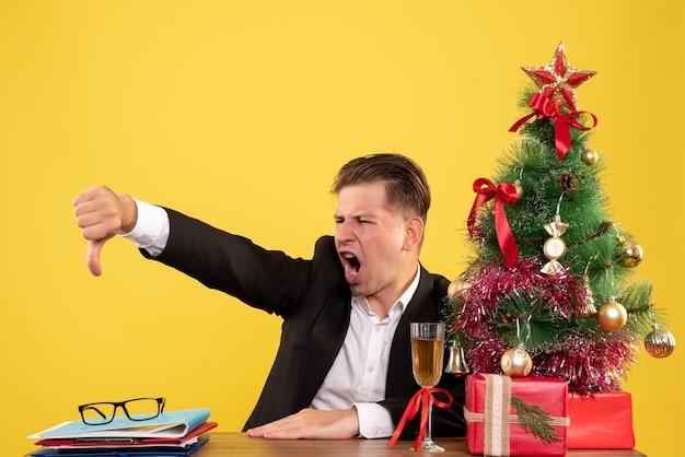 Vue de face travailleur masculin assis derrière sa table de travail mécontent