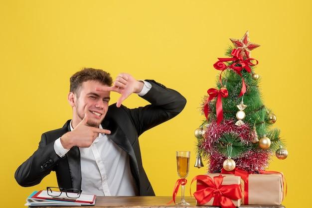 Vue de face travailleur masculin assis derrière son lieu de travail avec une bonne humeur sur jaune