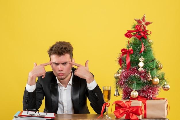 Vue de face travailleur masculin assis derrière son lieu de travail sur bureau jaune couleur émotion emploi de bureau nouvel an noël