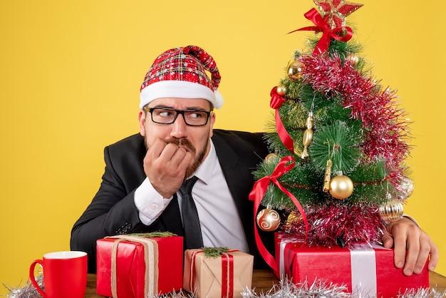 Vue de face travailleur masculin assis derrière son lieu de travail avec des cadeaux sur le bureau jaune bureau couleur travail noël cadeau de nouvel an
