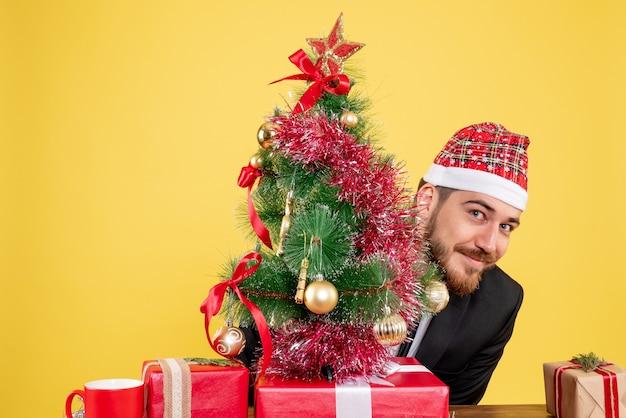 Vue de face travailleur masculin assis derrière son lieu de travail avec des cadeaux sur le travail de bureau jaune noël couleur cadeau nouvel an