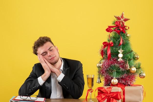 Vue de face travailleur masculin assis derrière son lieu de travail dormir sur jaune