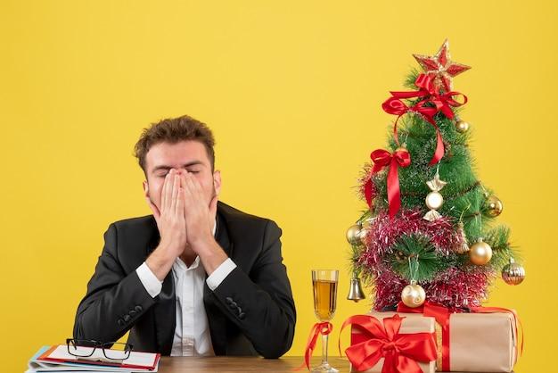 Vue de face travailleur masculin assis derrière son lieu de travail fatigué sur jaune