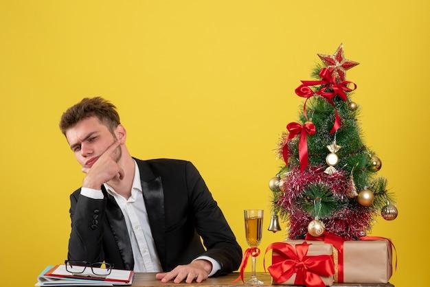 Vue de face travailleur masculin assis derrière son lieu de travail sur jaune