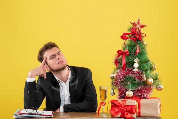 Vue de face travailleur masculin assis derrière son lieu de travail pensant sur jaune