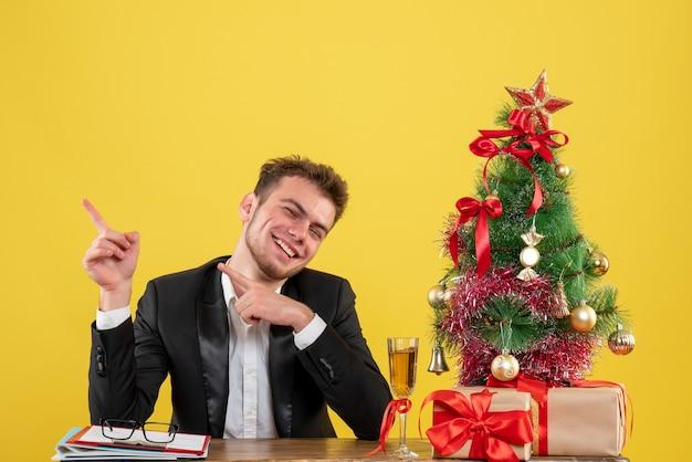 Vue de face travailleur masculin assis derrière son lieu de travail souriant sur jaune