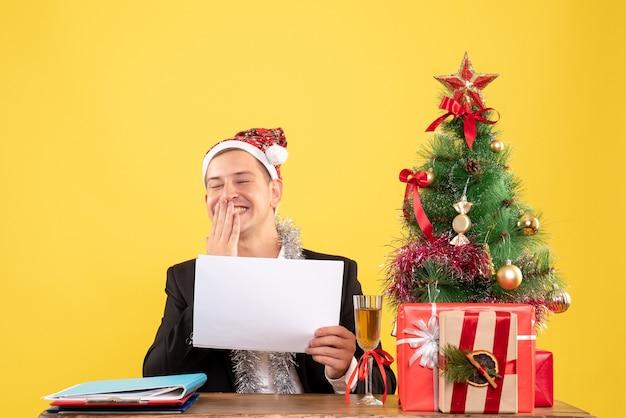 Vue de face travailleur masculin assis tenant des documents et riant