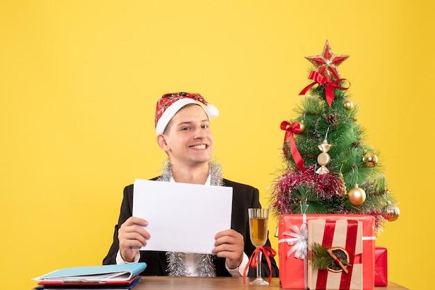 Vue de face travailleur masculin assis tenant des documents souriant