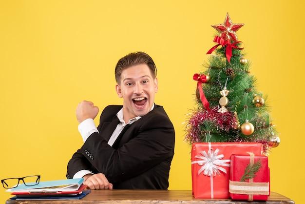 Vue de face travailleur masculin en costume assis derrière sa table de travail se réjouissant