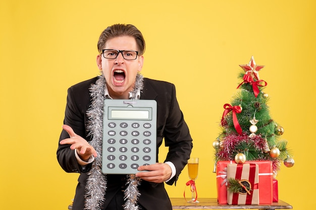 Vue de face travailleur masculin en costume debout et tenant la calculatrice