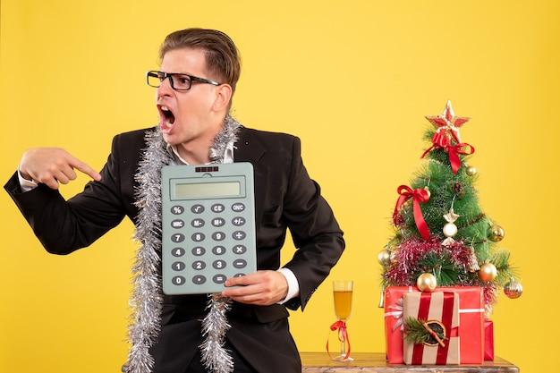 Vue de face travailleur masculin en costume debout et tenant en colère la calculatrice