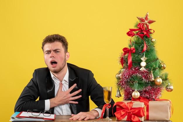 Vue de face travailleur masculin derrière son lieu de travail avec présente un problème cardiaque sur jaune