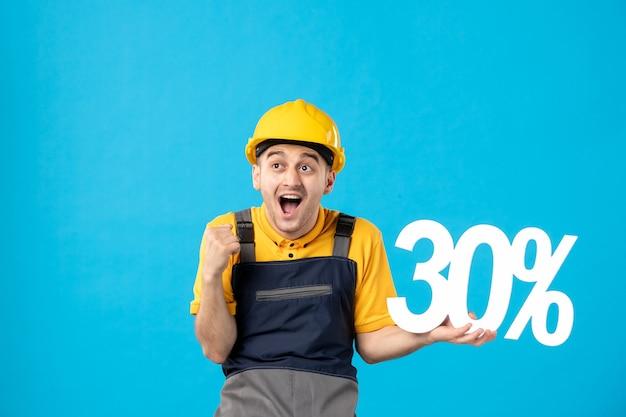 Vue de face travailleur masculin excité en uniforme avec écriture sur bleu