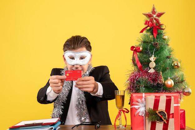 Vue de face travailleur masculin portant un masque de fête et tenant une carte bancaire