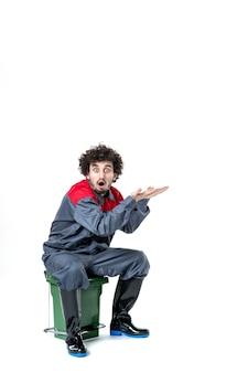 Vue de face d'un travailleur masculin en uniforme assis sur une petite poubelle sur un mur blanc