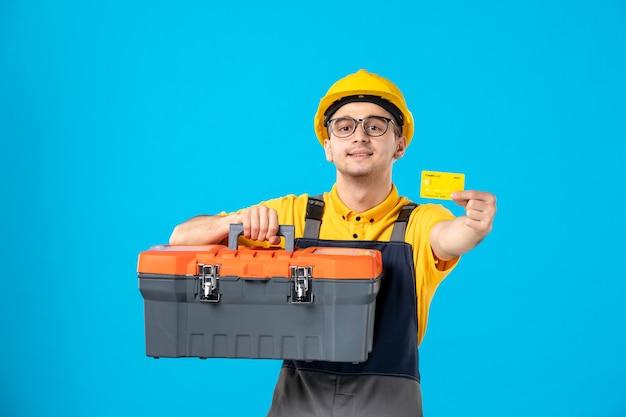 Vue de face travailleur masculin en uniforme et casque boîte à outils et carte bancaire sur bleu