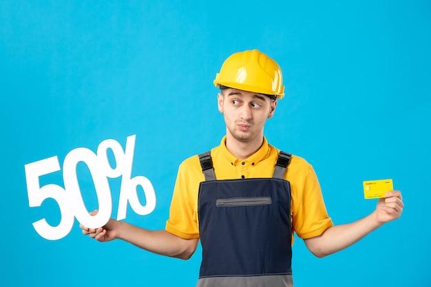 Vue de face travailleur masculin en uniforme avec écriture et carte de crédit sur le bleu